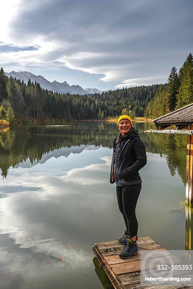 Young female hiker standing on a footbridge at Grubsee, near Kruen, Karwendel, Upper Bavaria, Bavaria, Germany, Europe