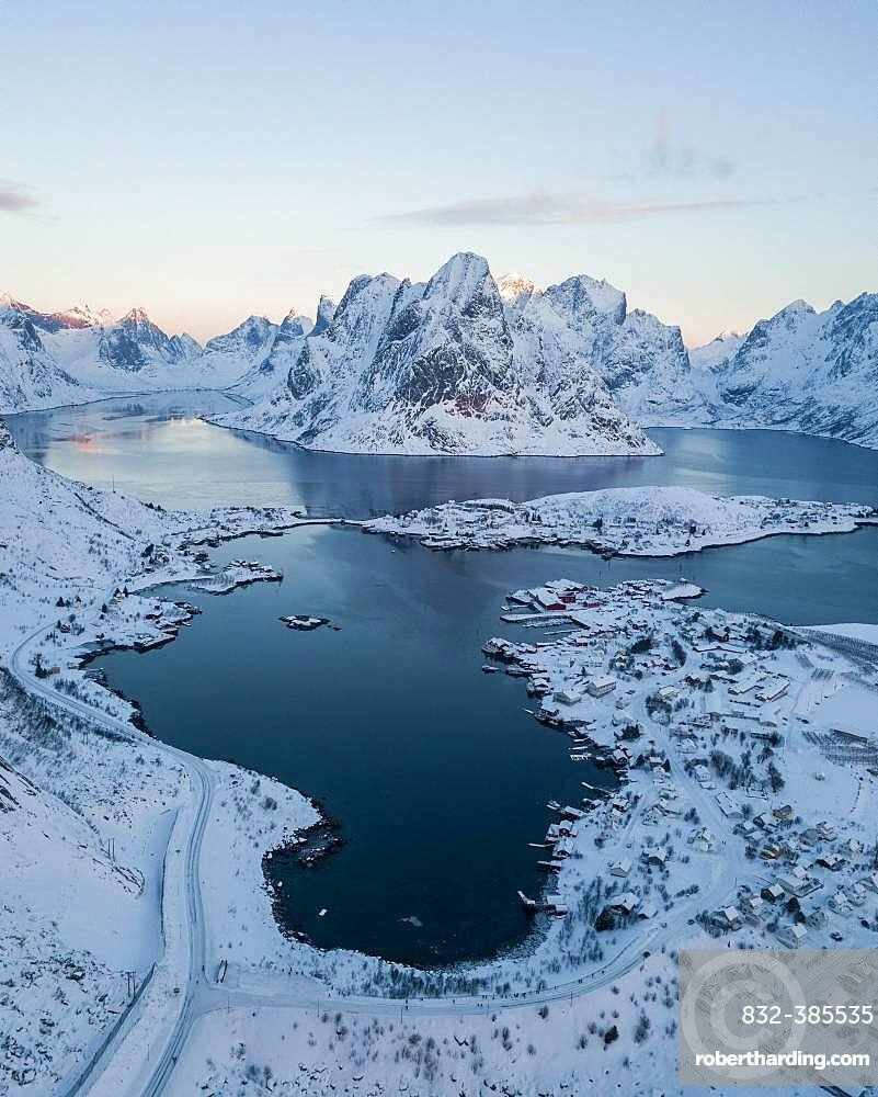 Snow-covered mountains at the fjord with village Reine, drone shot, Lofoten, Norway, Europe