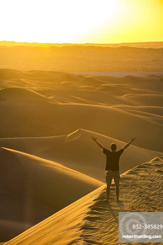 Man enjoying the sunset in the giant sanddunes of the Sahara, Timimoun, Algeria, Africa