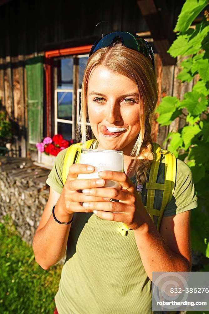 Young female hiker drinks buttermilk at the Kraftalm, Hohe Salve, Itter, Kitzbuehel Alps, Tyrol, Austria, Europe