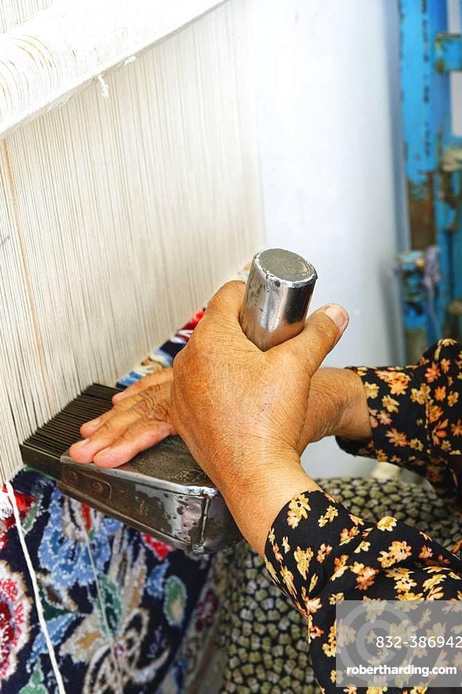 Iranian woman weaving a carpet, Na'in, Isfahan Province, Iran, Asia