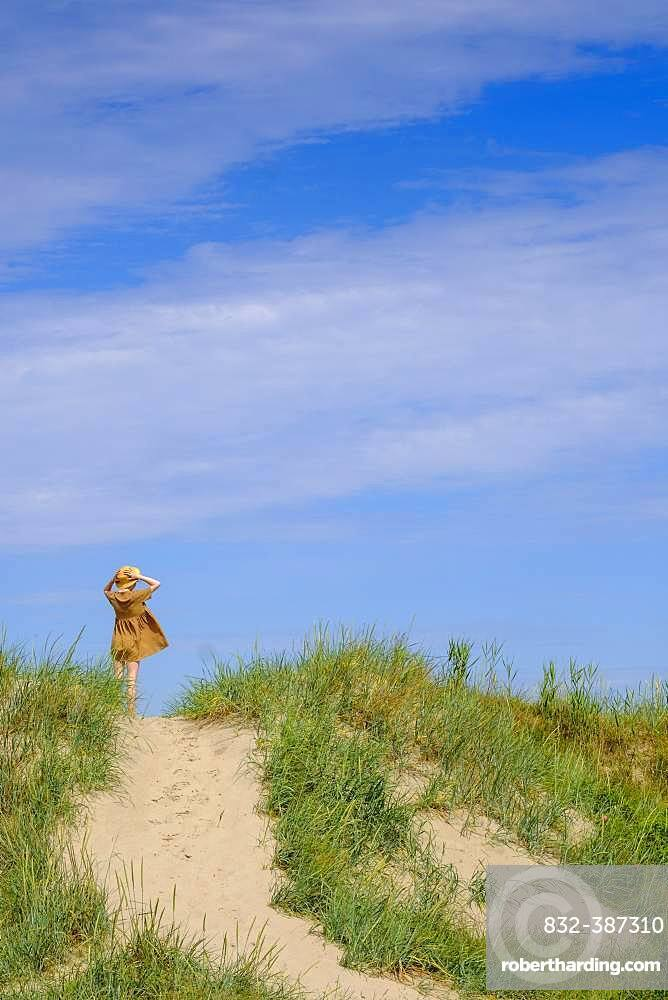 Young woman with sun hat, in the dunes at the sandy beach, Farhult, Skane, Skane, Skane laen, southern Sweden, Sweden, Europe