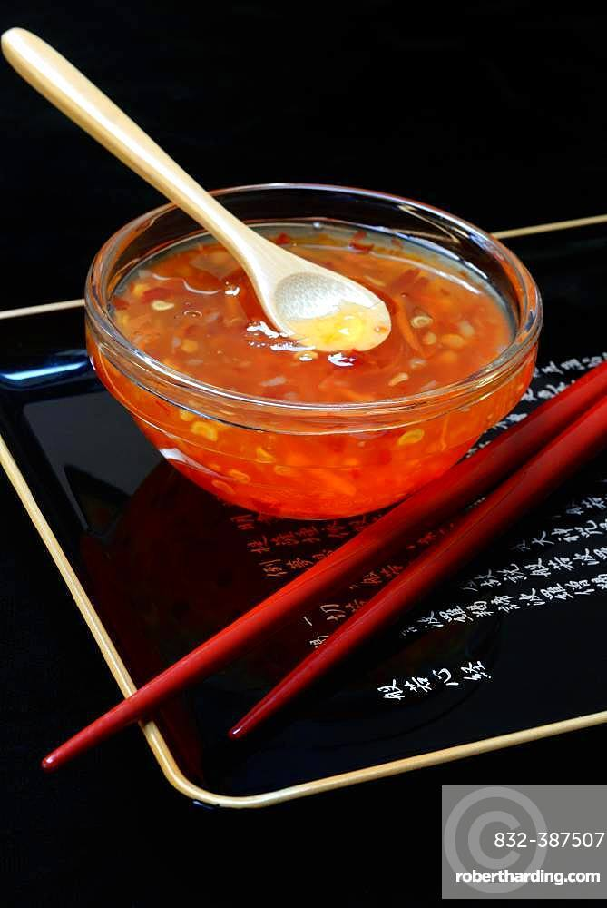 Chilli sauce with spoon in glass bowl and red chopsticks, Germany, Europe