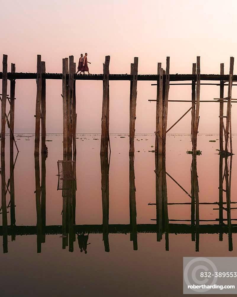 Buddhist monks walk across the U-leg bridge in red robes as the sun rises, Mandalay, Myanmar, Asia