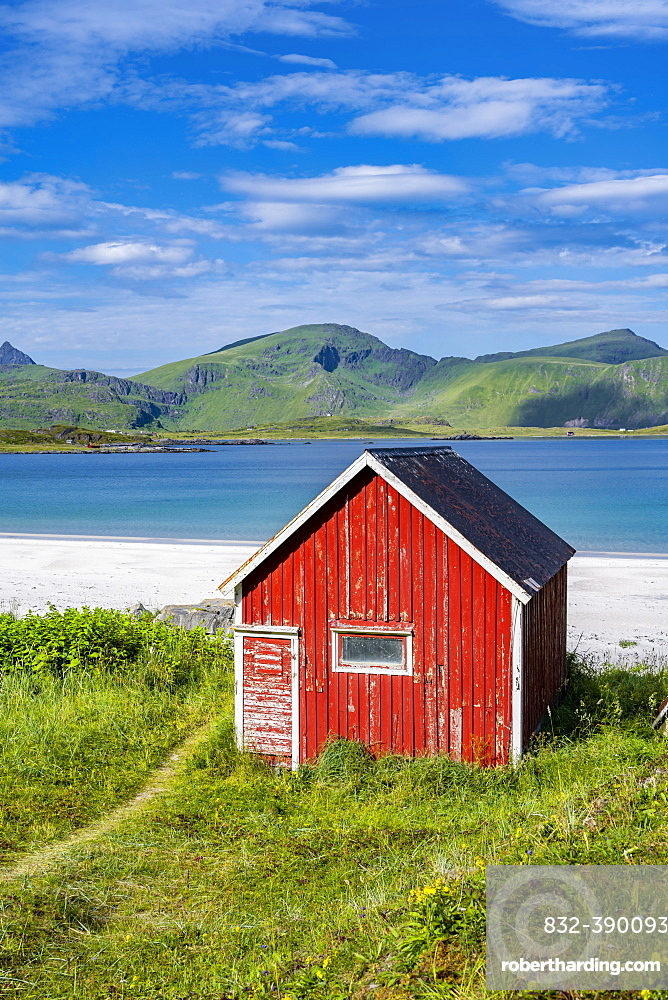 Rorbuer, traditional wooden house on sandy beach Rambergstranda, mountains and sea, Junesvika, Lofoten, Nordland, Norway, Europe