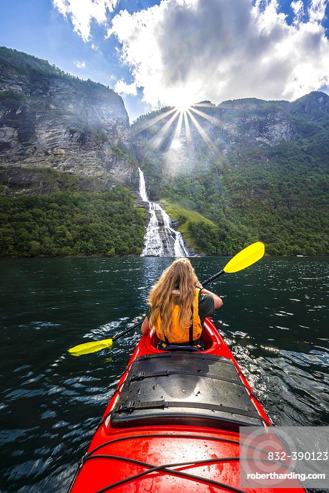 Young woman paddling in a kayak, Freier waterfall, Geirangerfjord, near Geiranger, Norway, Europe