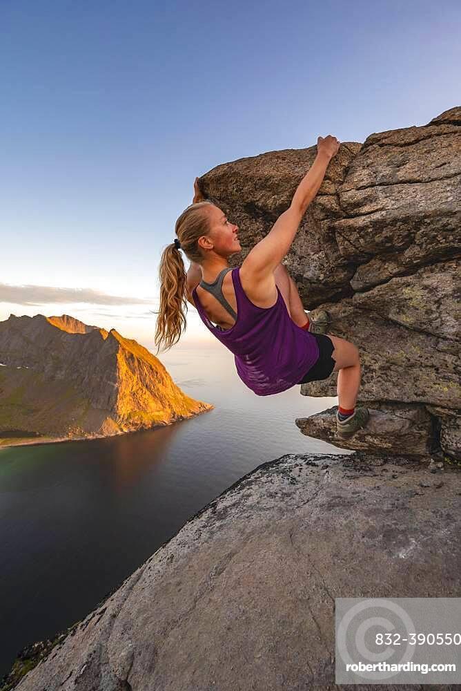 Evening atmosphere, Young woman bouldering, Climbing, Peak of Ryten, Sea, Kvalvika beach and mountains, Fredvang, Lofoten, Nordland, Norway, Europe