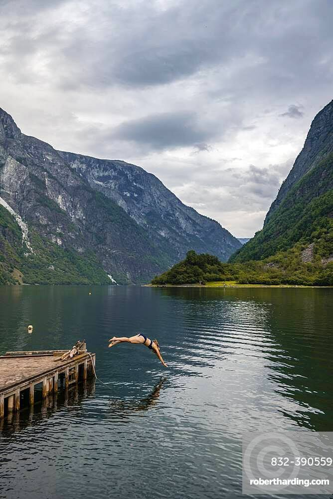 Woman jumping into the water, Naeroyfjord, Aurland, Sogn og Fjordane, Norway, Europe