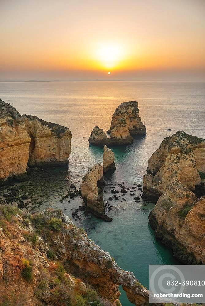 Rugged rocky coast with cliffs of sandstone, rock formations in the sea, Ponta da Piedade, dawn at sunrise, Algarve, Lagos, Portugal, Europe