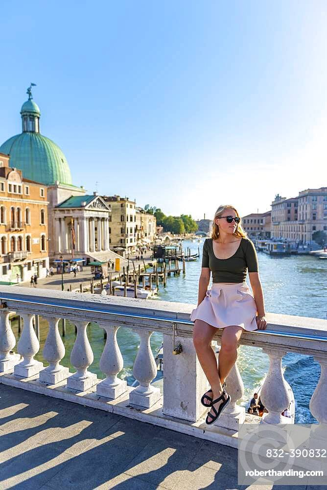Young woman sitting on bridge railing on the Grand Canal, Church of San Simeone Piccolo, Ponte degli Scalzi, Venice, Veneto, Italy, Europe