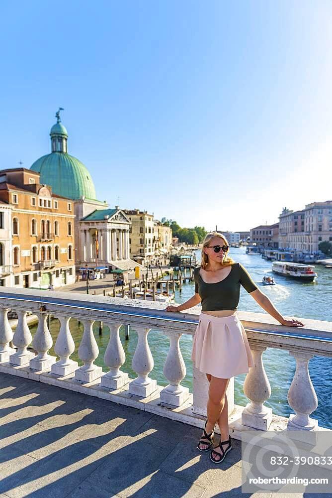 Young woman leaning against bridge railing on the Grand Canal, Church of San Simeone Piccolo, Ponte degli Scalzi, Venice, Veneto, Italy, Europe