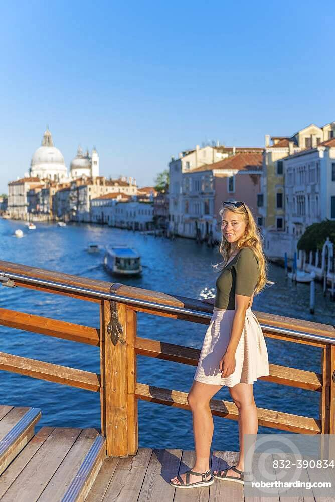 Young woman at the Ponte dell'Accademia, view of the Grand Canal and the Basilica of Santa Maria della Salute, Venice, Veneto, Italy, Europe