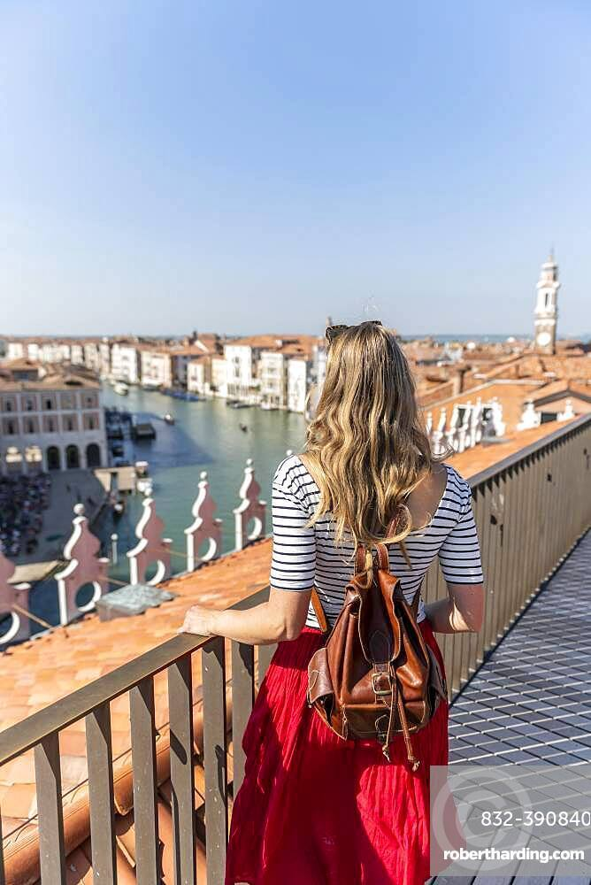 Young woman with red skirt, view from the panoramic roof of the Fondaco dei Tedeschi, view on Grand Canal, Venice, Veneto, Italy, Europe