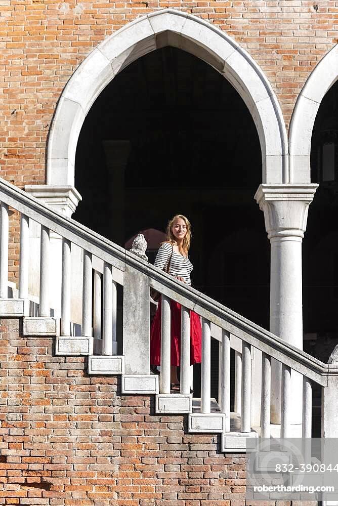 Young woman walking down a staircase, Mercato di Rialto, Venice, Veneto, Italy, Europe