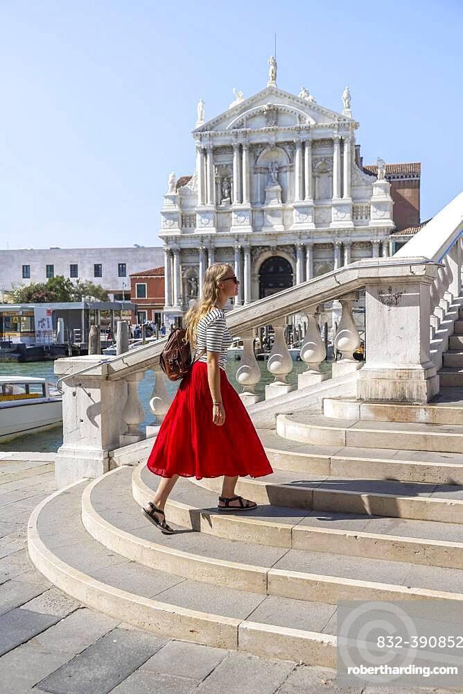 Young woman with red skirt walks over a bridge at the Grand Canal, Church of Santa Maria di Nazareth, Ponte degli Scalzi, Venice, Veneto, Italy, Europe