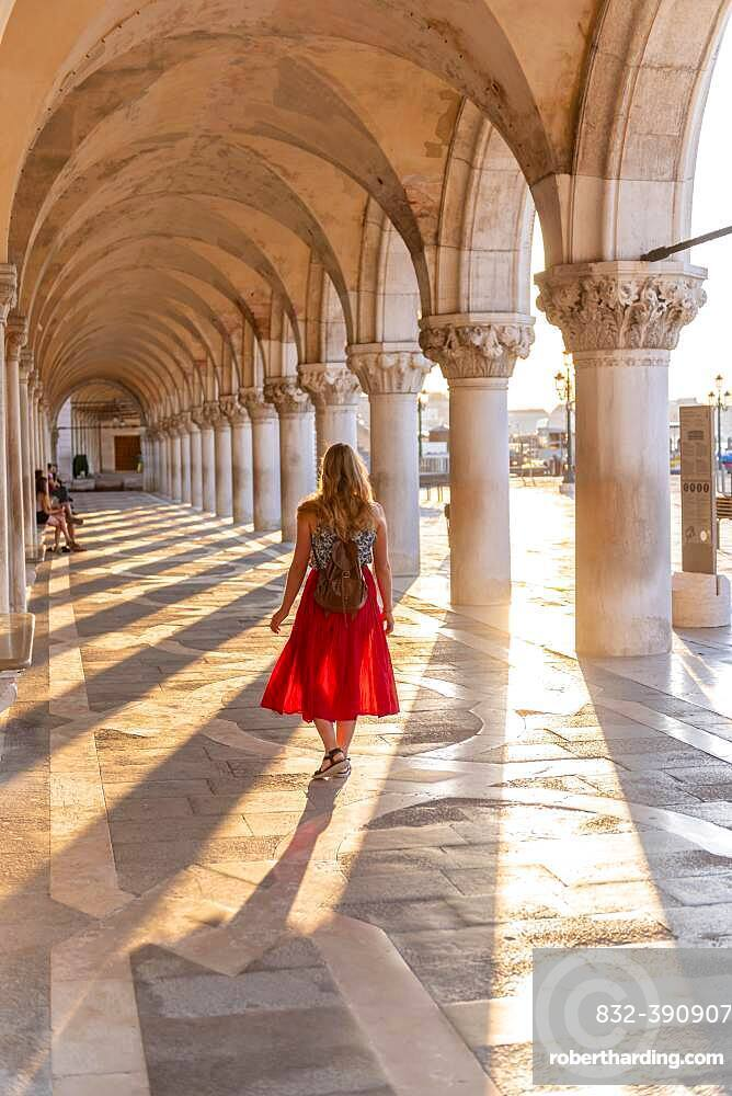 Young woman in the portico at the Doge's Palace, St. Mark's Square, Venice, Veneto, Italy, Europe