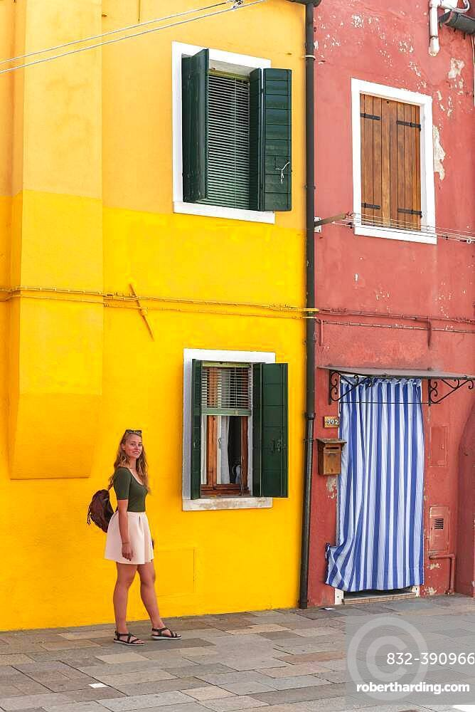 Young woman in front of colorful house, colorful house facades, tourist on Burano island, Venice, Veneto, Italy, Europe
