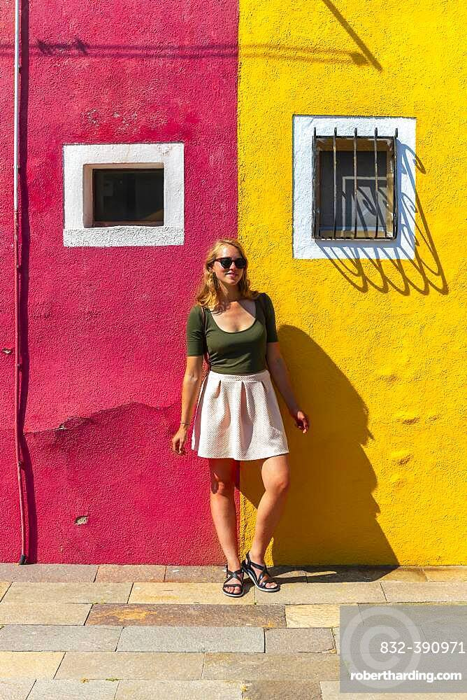 Young woman in front of colorful house, red and yellow house facade, Burano Island, Venice, Veneto, Italy, Europe