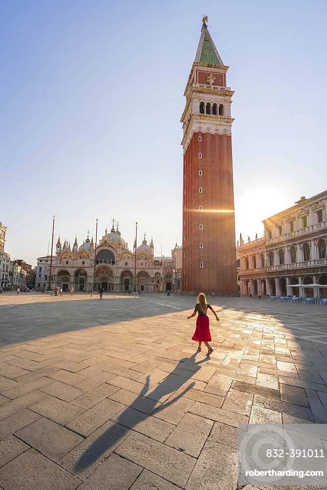 Young woman, tourist with red dress at St. Mark's Square, sun shines on St. Mark's Square with Campanile di San Marco, Venice, Veneto, Italy, Europe