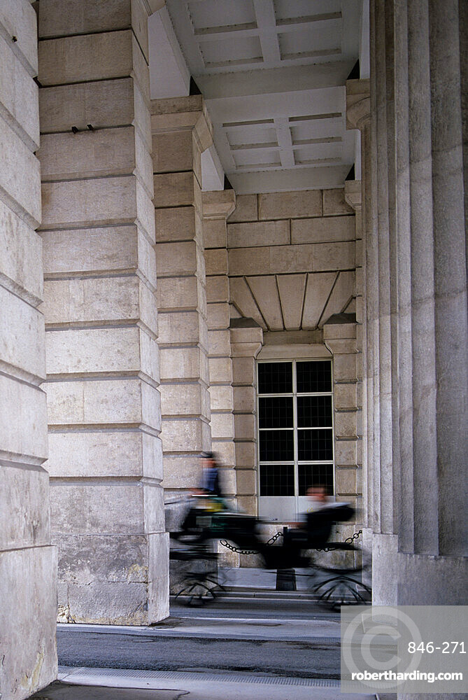 Carriage passing between classical columns, Vienna, Austria, Europe