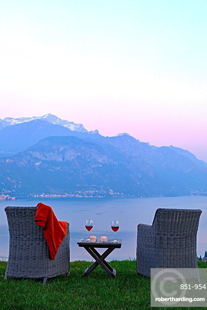 Armchairs and red wine with views of Lake Como at sunset.