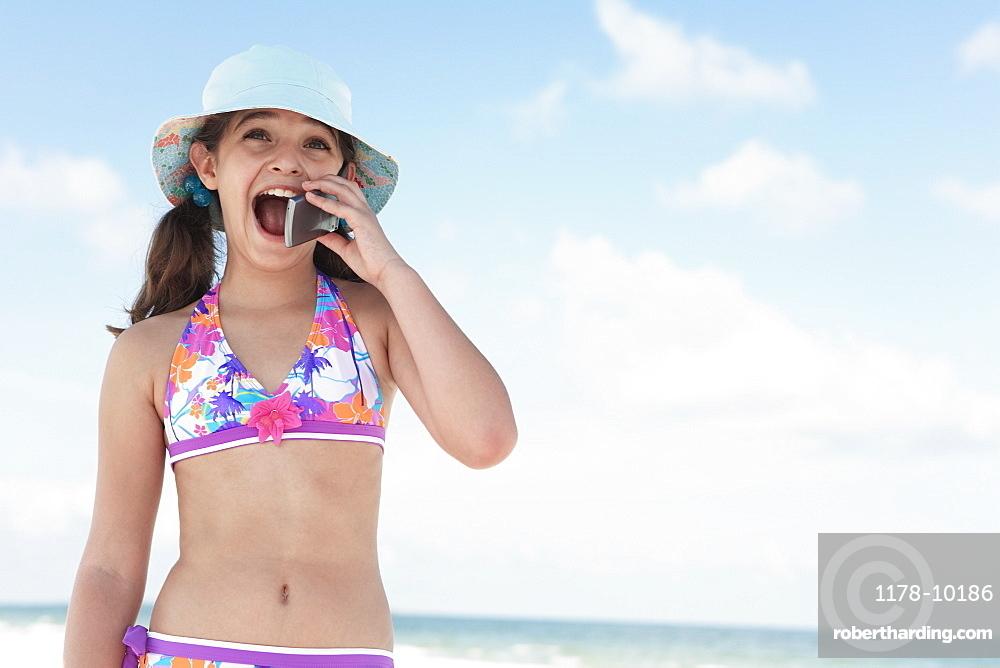 Girl on beach talking on cell phone