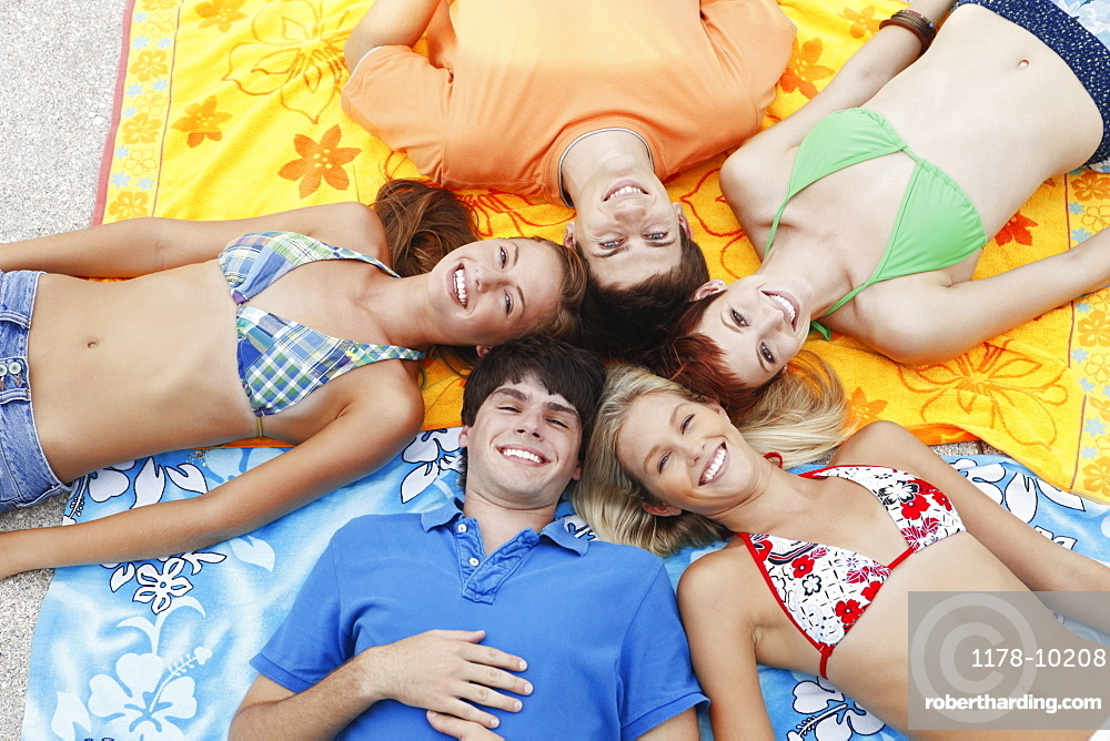Friends lying down on beach towels