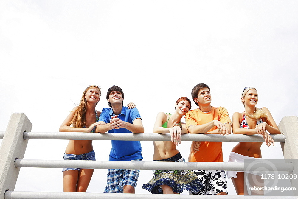 Friends leaning on boardwalk railing