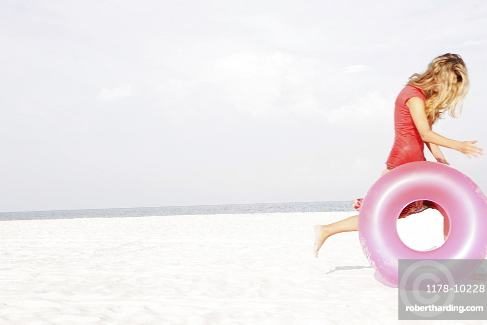 Teenage girl rolling inflatable ring on beach