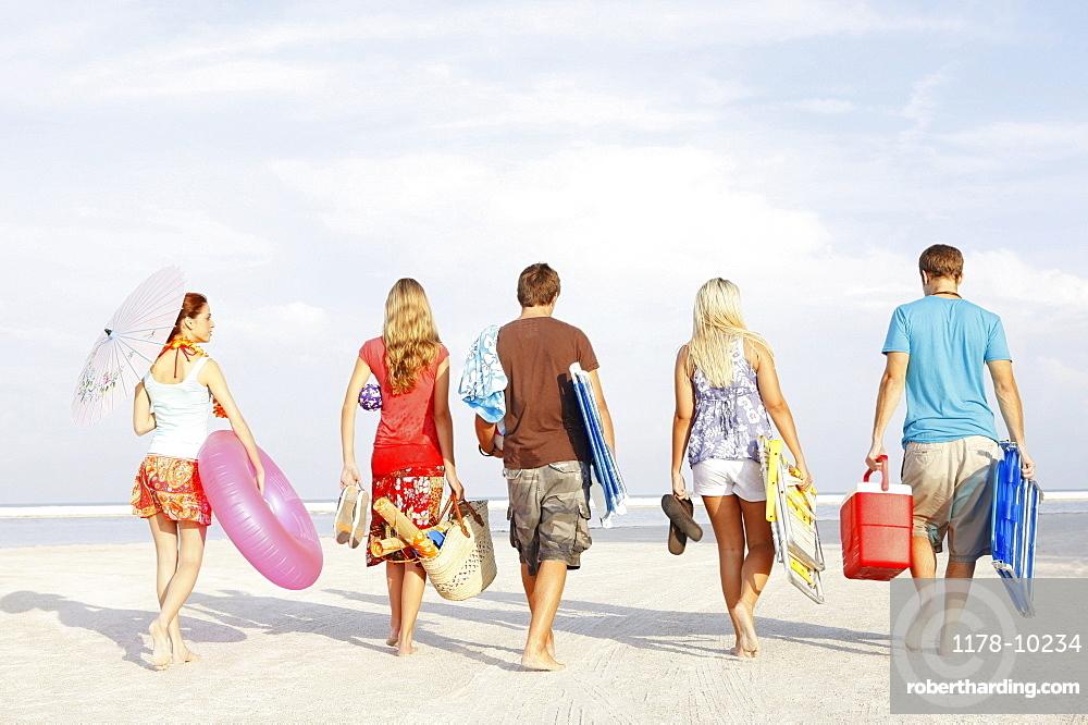 Friends walking with beach essentials