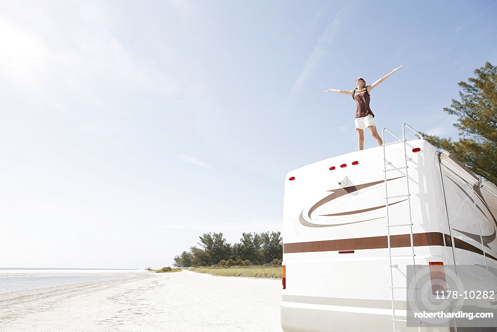 Young woman standing on top of motor home