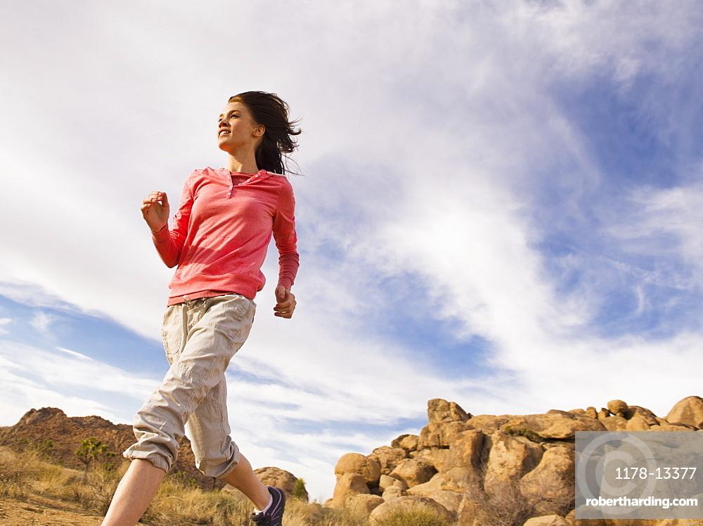 USA, California, Joshua Tree National Park, Young woman jogging in desert, USA, California, Joshua Tree National Park