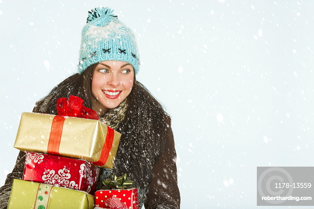 Studio portrait of woman in winter clothing carrying presents