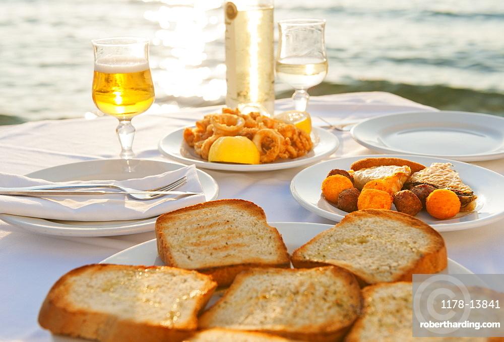 Greece, Cyclades Islands, Mykonos, Calamari appetizer on set table by sea