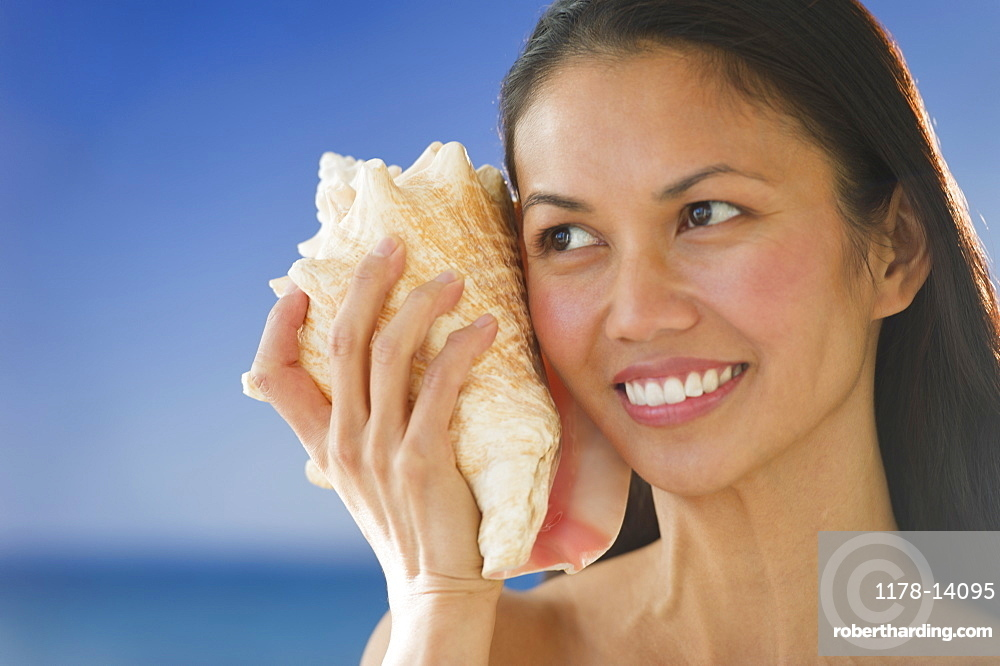 USA, New Jersey, Jersey City, Woman listening to conch shell near sea