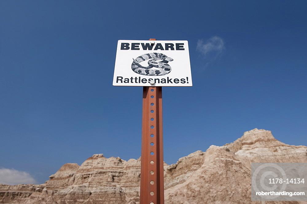USA, South Dakota, Badlands National Park, Rattlesnake warning sign against sky, mountain in background