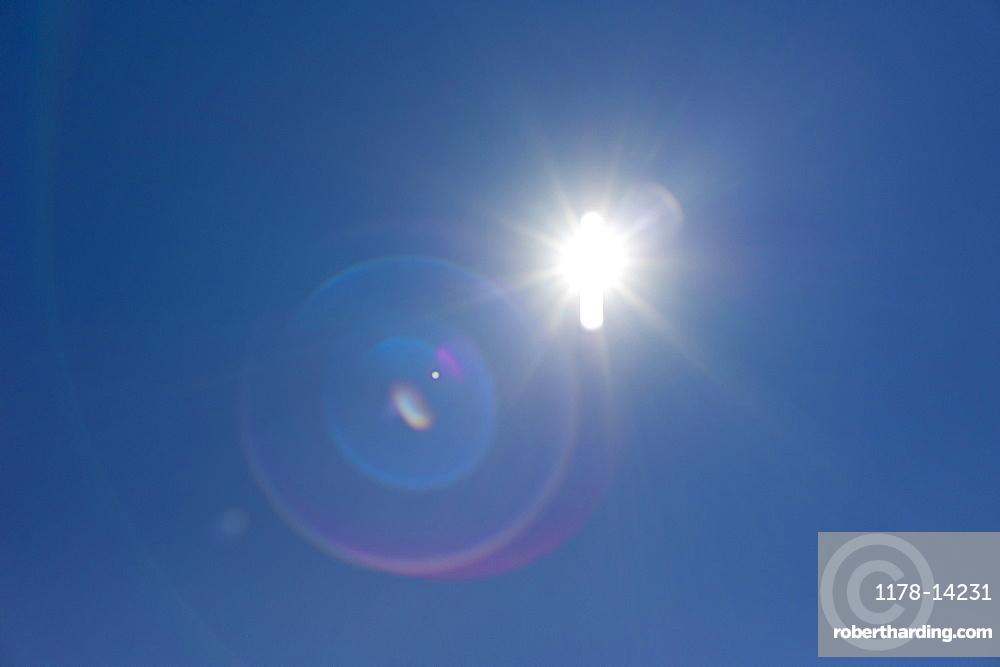 Flare of light in blue sky