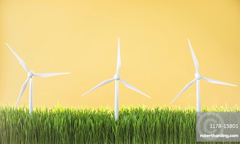 Model wind turbines in grass on yellow background