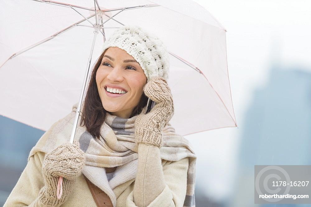 Woman with umbrella using phone