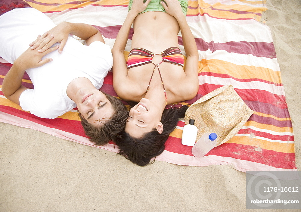 Couple laying on blanket at beach