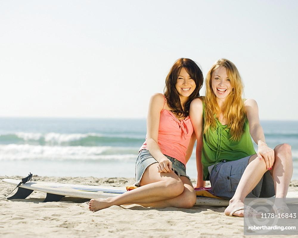 Multi-ethnic women sitting on surf board