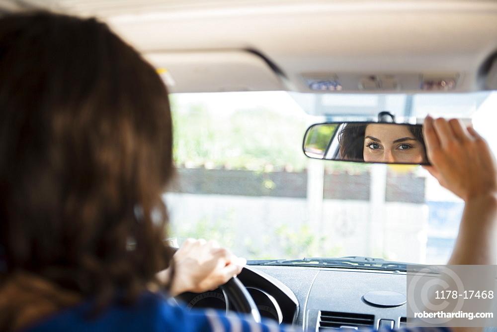 Woman adjusting rear view mirror in car