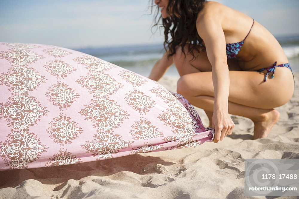 Woman preparing blanket on beach, Rockaway Beach, New York