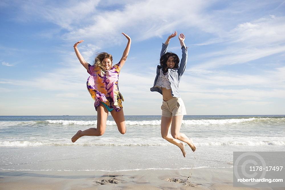 Two young women jumping on beach, Rockaway Beach, New York