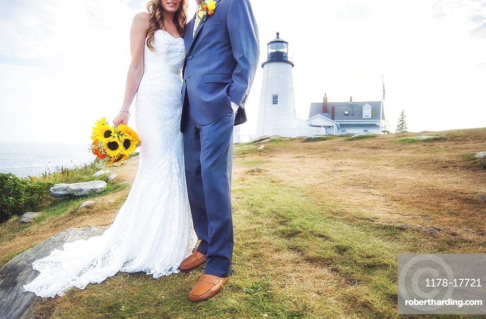 Low section of married couple, lighthouse in background, USA, Maine, Bristol