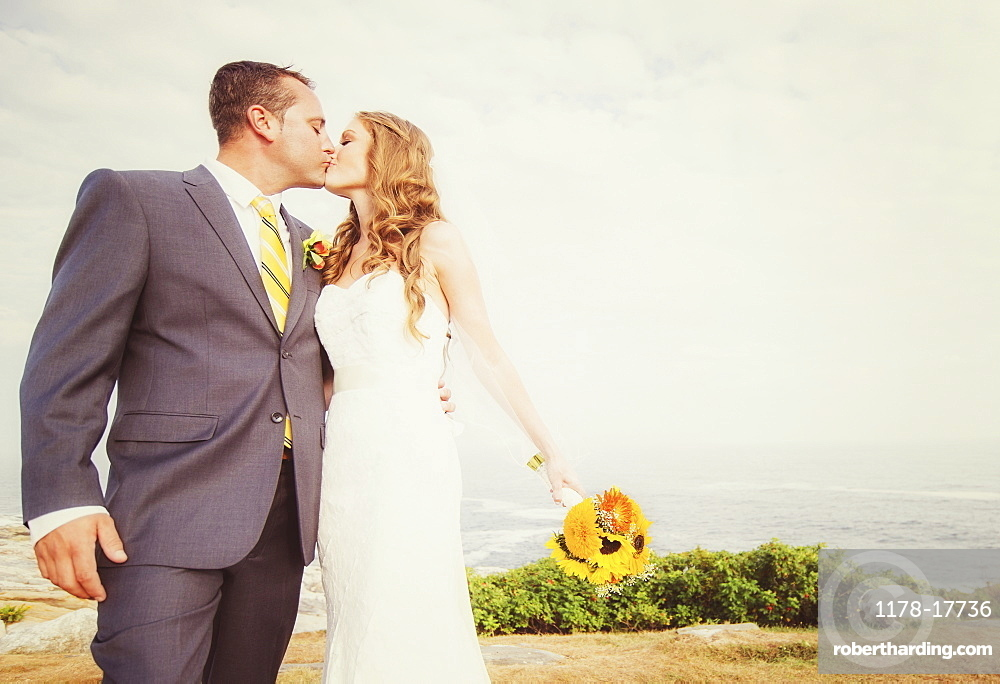 Portrait of married couple kissing, sea in background, USA, Maine, Bristol