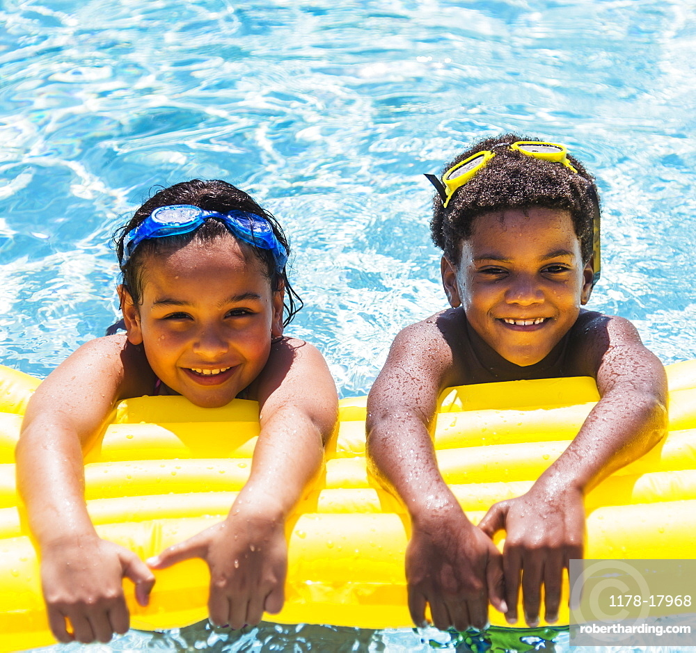 Portrait of kids( 6-7, 8-9) with pool raft