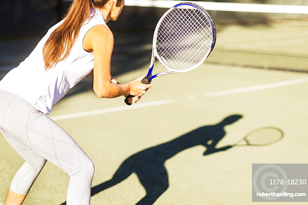 High-section shot of young woman playing tennis in outdoor court