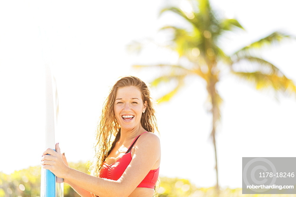 Portrait of young woman holding surfboard on beach, Jupiter, Florida
