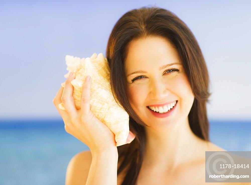 Portrait of young woman listening to seashell, studio shot